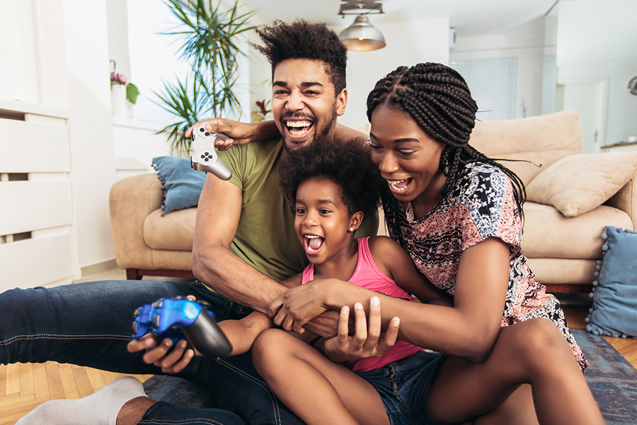 Personal Insurance - Smiling Happy Family Having Fun While Sitting on the Floor in Front of Couch Playing Video Games Together